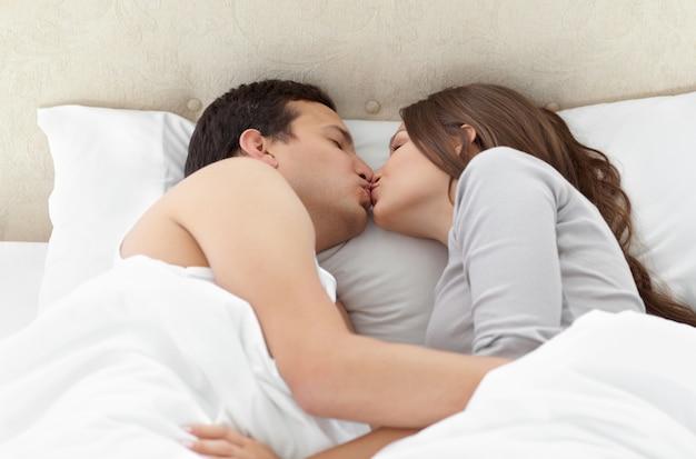 Encantadora pareja besándose en los brazos de la otra en la cama