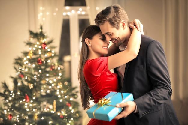 Encantadora pareja besándose en casa, mientras celebraba la navidad