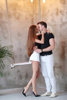Encantadora pareja besándose en columpio