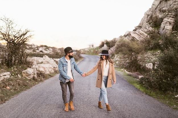 Encantadora pareja caminando por una carretera