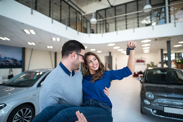Encantadora pareja caucásica comprando vehículo nuevo.