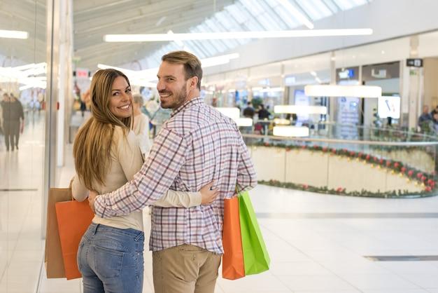 Encantadora pareja caucásica haciendo compras en un centro comercial