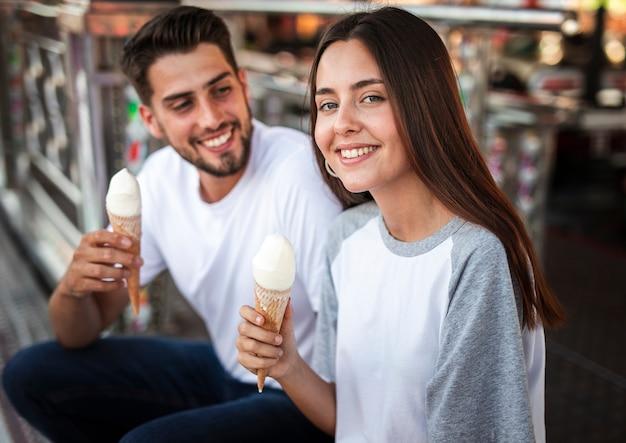 Encantadora pareja comiendo helados en la feria