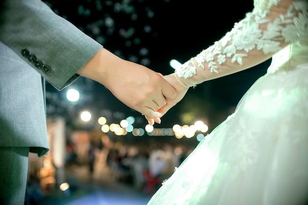 Encantadora pareja se dan la mano en la noche romántica