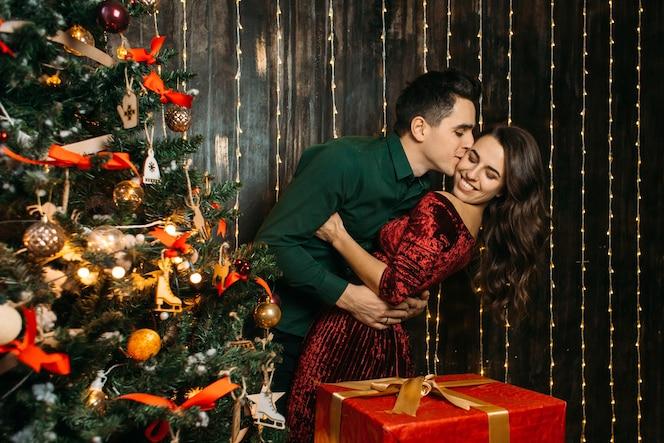 Encantadora pareja de enamorados abrazándose cerca de árbol de navidad