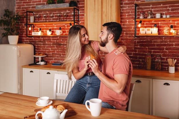 Encantadora pareja desayunando en la cocina