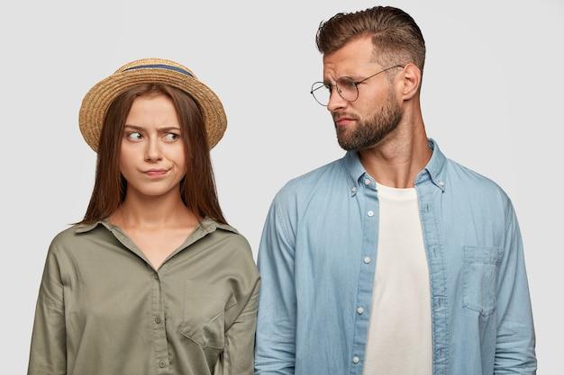Encantadora pareja disgustada posando contra la pared blanca
