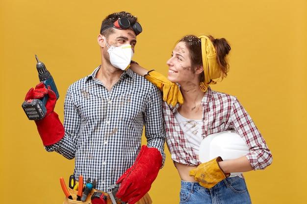 Encantadora pareja de enamorados haciendo trabajos de construcción juntos. mujer joven vestida con camisa a cuadros y jeans mirando con una sonrisa a su esposo que es talentoso montador. buenas relaciones y trabajo manual