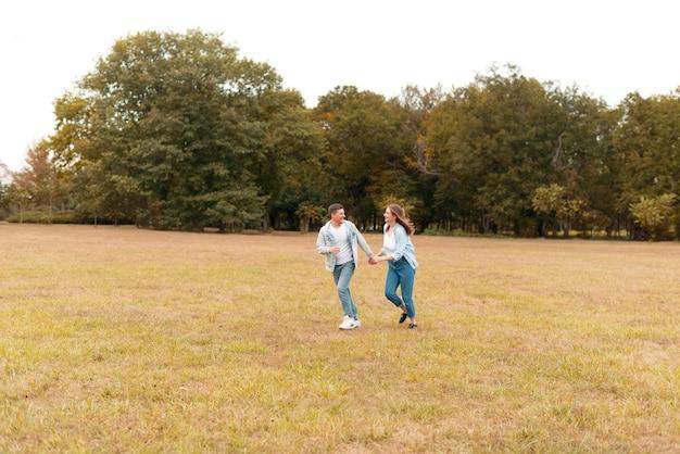 Encantadora pareja encantadora joven con ventilador al aire libre en el parque