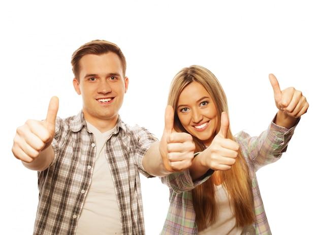Encantadora pareja con gesto de pulgar hacia arriba aislado en blanco