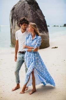 Encantadora pareja de hipster con estilo joven enamorada en la playa tropical durante las vacaciones