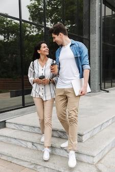 Encantadora pareja hombre y mujer en ropa casual bebiendo café para llevar mientras pasea por las calles de la ciudad