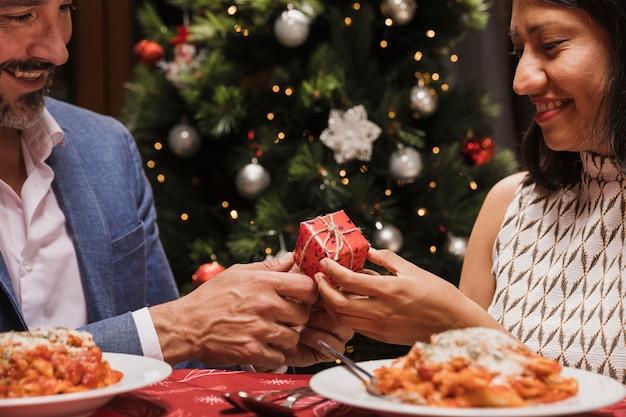 Encantadora pareja intercambiando regalos de navidad