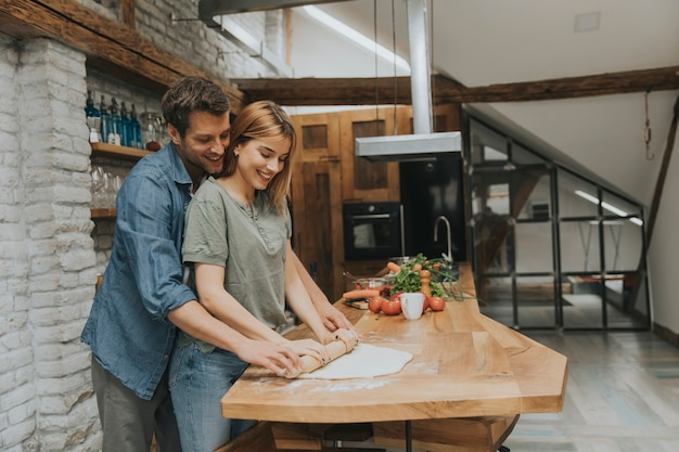 Encantadora pareja joven alegre que cocina la cena juntos y se divierte en la cocina rústica