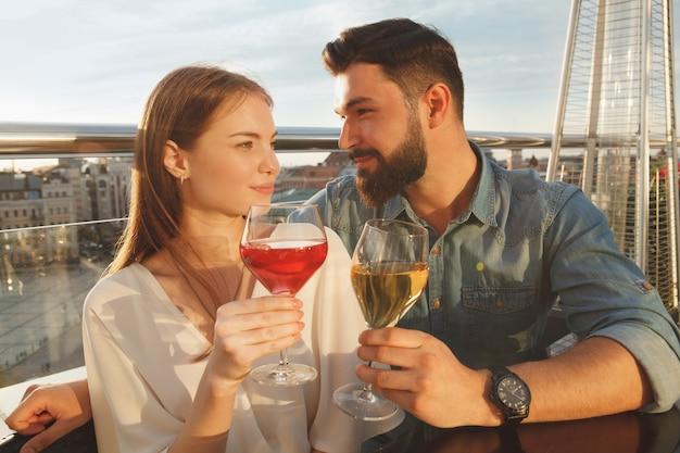 Encantadora pareja joven celebrando el aniversario, bebiendo vino en la puesta de sol al aire libre