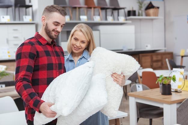 Encantadora pareja joven comprando ropa de cama juntos en la tienda de artículos para el hogar