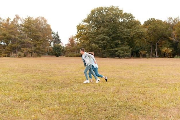 Encantadora pareja joven corriendo al aire libre durante el otoño