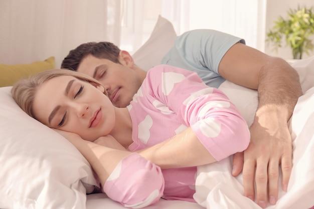 Encantadora pareja joven durmiendo en la cama en casa