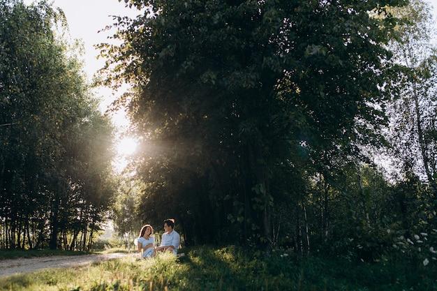 Encantadora pareja joven esperando descansar en la tela escocesa debajo del árbol verde