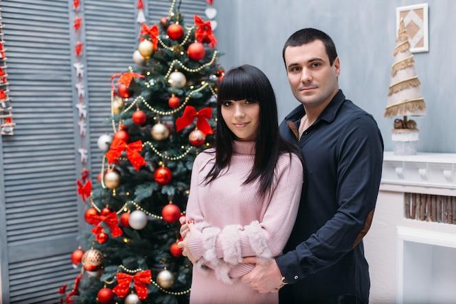 Encantadora pareja joven feliz posa ante un árbol de navidad rojo en un rincón acogedor