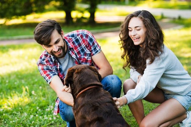 Encantadora pareja joven jugando con su perro en el jardín