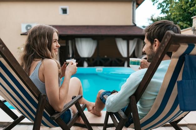 Encantadora pareja joven pasar tiempo juntos en casa cerca de la piscina mientras charla y disfruta del té