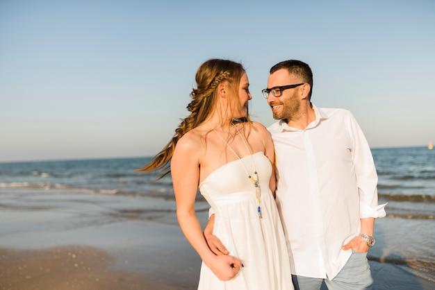 Encantadora pareja joven de pie cerca de la orilla del mar en la playa