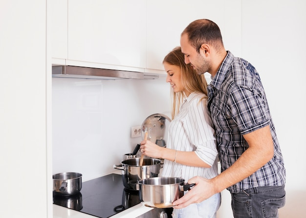 Encantadora pareja joven preparando la comida en la cocina moderna