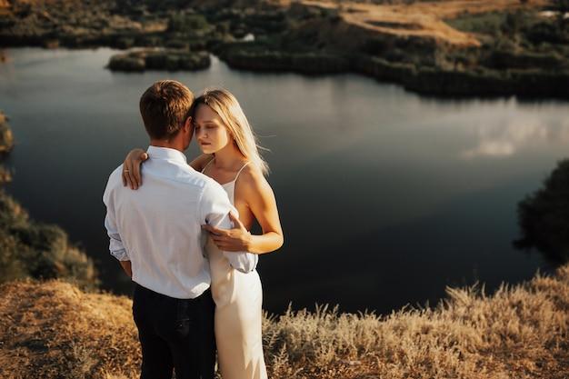 Encantadora pareja joven en ropa elegante abrazando cerca del lago en la cima de la colina.