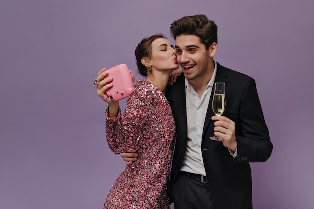 Encantadora pareja joven en ropa de fiesta divirtiéndose con la cámara, haciendo fotos, bebiendo vino y posando encantadora contra la pared de color púrpura claro