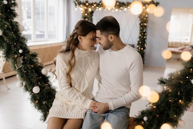 Encantadora pareja joven en ropa de hogar blanca acogedora posa en una habitación con árbol de navidad