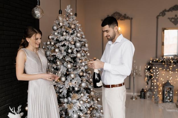 Encantadora pareja joven en ropa de lujo posa con copas de champán ante un árbol de navidad