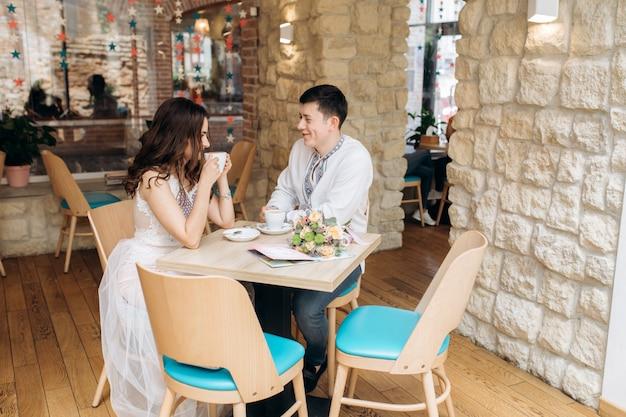 Encantadora pareja joven se sienta en una mesa en un acogedor café