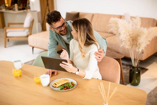 Encantadora pareja joven con tableta digital y desayunando en la cocina