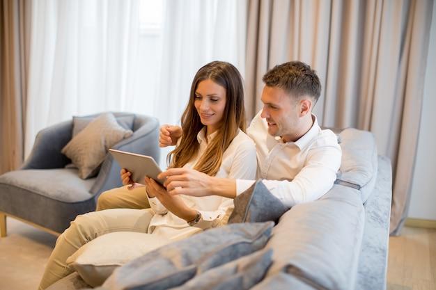 Encantadora pareja joven con tableta digital en la habitación
