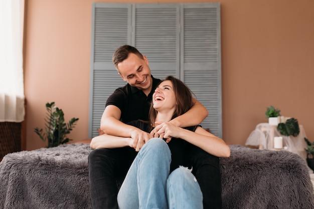 Encantadora pareja joven vestida en estilo casual se sienta en el piso