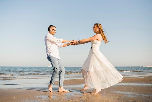 Encantadora pareja de jóvenes bailando juntos cerca de la costa en la playa