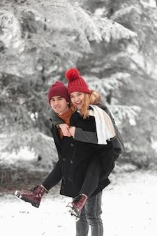 Encantadora pareja jugando afuera en el invierno