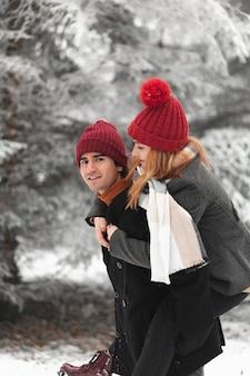 Encantadora pareja jugando al aire libre en invierno