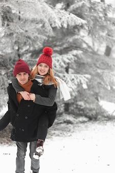 Encantadora pareja jugando en la nieve