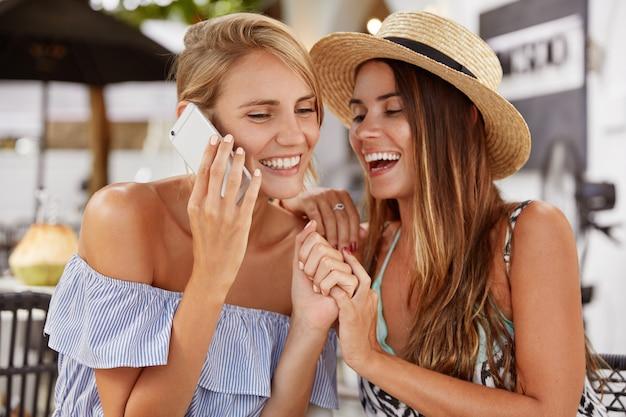 Encantadora pareja de lesbianas divertirse, reír con alegría y mantener las manos juntas, tener una conversación móvil