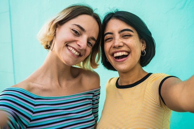 Encantadora pareja de lesbianas tomando una selfie.