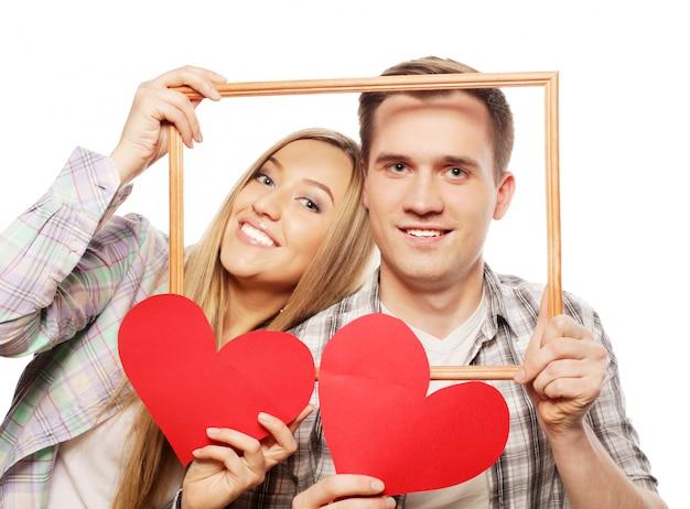 Encantadora pareja con marco y corazones rojos