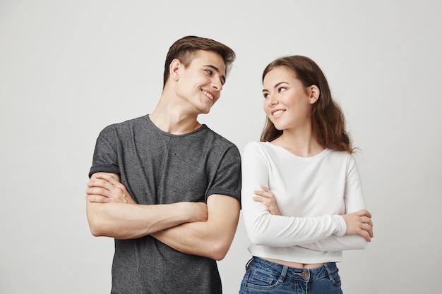 Encantadora pareja mirándose con las manos cruzadas mientras sonríe.