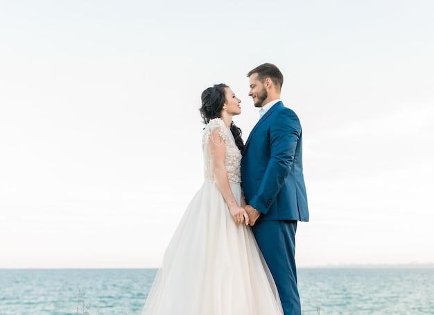 Encantadora pareja de novios, el novio y la novia, están caminando en la orilla del mar, corriendo, riendo, divirtiéndose. descanso de bodas, relax concepto de luna de miel.