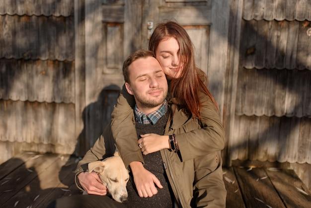 Encantadora pareja pasar el día de otoño al aire libre con su perro