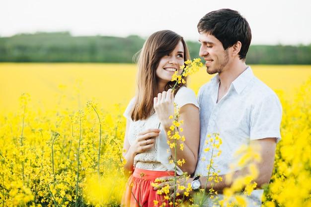 Encantadora pareja de pie cerca el uno del otro, abrazarse y mirar a los ojos, posar contra el campo amarillo