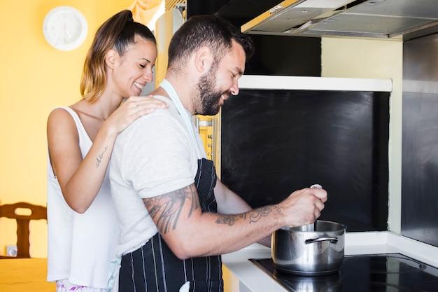Encantadora pareja preparando la comida en la estufa de inducción