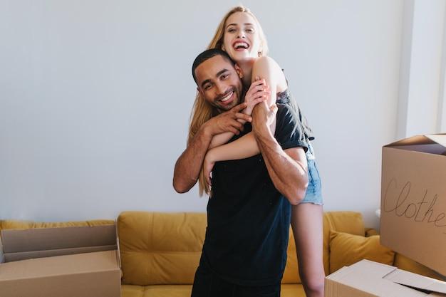 Encantadora pareja que acaba de mudarse, feliz de comenzar una nueva vida en casa, piso, empacando personal en cajas de cartón. señorita abrazando a su hombre desde atrás