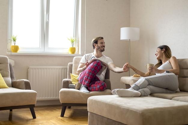 Encantadora pareja romántica tomando café y teniendo una agradable conversación en casa